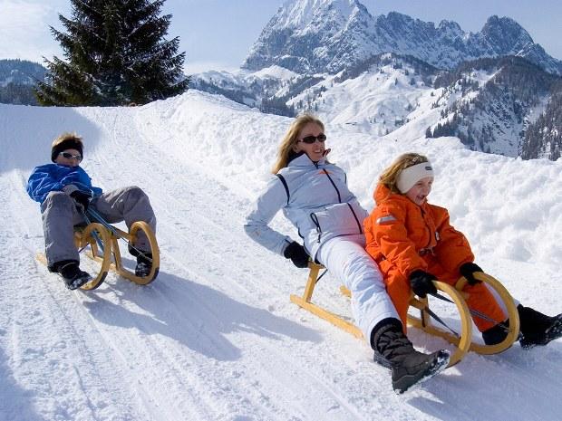 Rodeln mit Kindern und Erwachsenen im Schnee