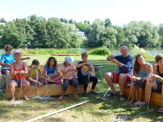 Kinder und Eltern üben gemeinsam Knoten im Familiencamp Loire