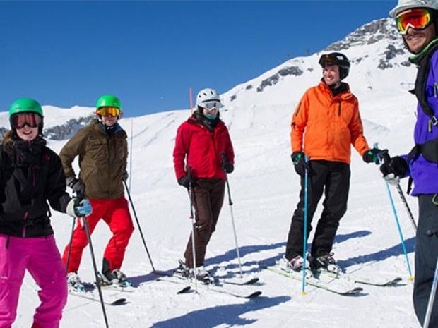 Erwachsenenskikurs pausiert auf der sonnigen Piste in Crnas Montana in der Schweiz