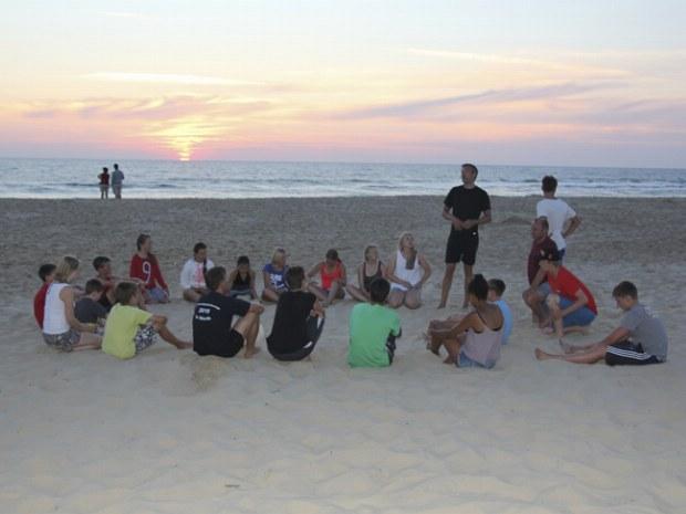 Teilnehmer des Seaside Camps am Strand in der Dämmerung